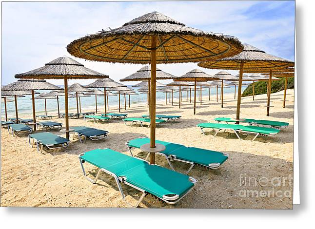 Umbrellas Greeting Cards - Beach umbrellas on sandy seashore Greeting Card by Elena Elisseeva