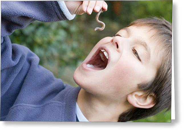 Boy Pretending To Eat An Earthworm Greeting Card by Ian Boddy
