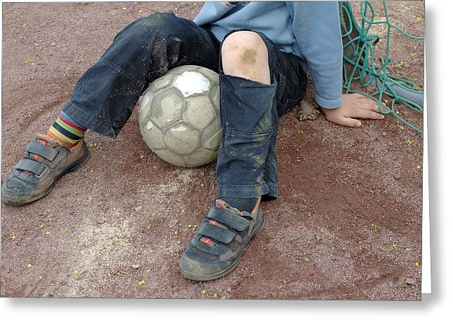 Pause Greeting Cards - Boy with soccer ball sitting on dirty field Greeting Card by Matthias Hauser