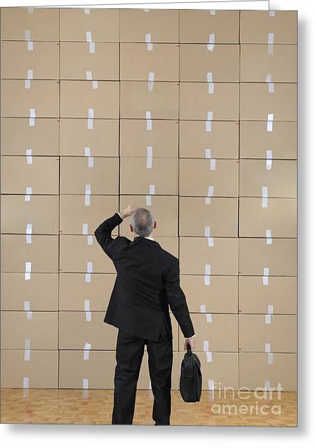Cardboard Greeting Cards - Businessman facing a cardboard boxes wall Greeting Card by Sami Sarkis