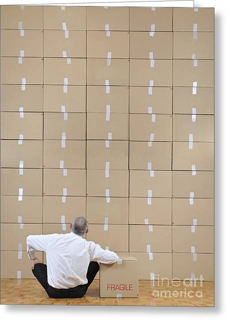 Cardboard Greeting Cards - Businessman seated facing cardboard boxes wall Greeting Card by Sami Sarkis