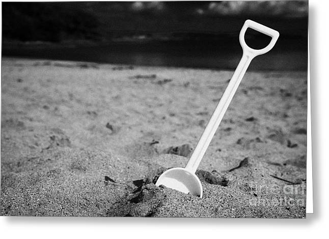 Child Toy Greeting Cards - Childs Toy Plastic Spade Stuck Into The Sand On A Beach Greeting Card by Joe Fox