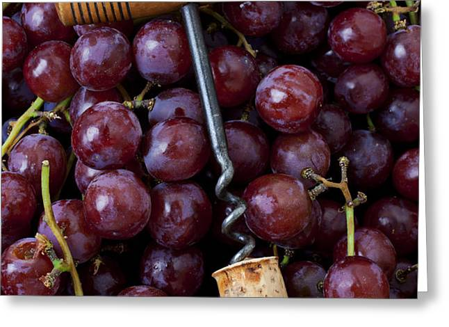 Corkscrew and wine cork on red grapes Greeting Card by Garry Gay