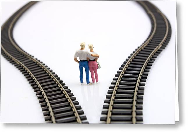 Choosing Photographs Greeting Cards - Couple two figurines between two tracks leading into different directions symbolic image for making decisions Greeting Card by Bernard Jaubert