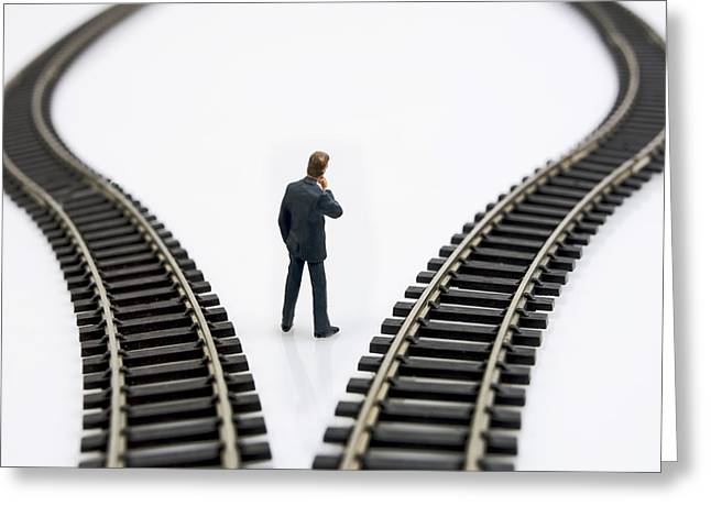 Businessmen Greeting Cards - Figurine between two tracks leading into different directions  symbolic image for making decisions Greeting Card by Bernard Jaubert