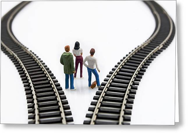Considering Greeting Cards - Figurines between two tracks leading into different directions symbolic image for making decisions. Greeting Card by Bernard Jaubert
