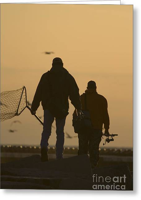 Fishing Enthusiast Greeting Cards - Fisherman walking on pier with nets and rods against the setting sun Greeting Card by Christopher Purcell