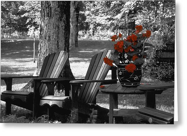 Empty Chairs Photographs Greeting Cards - Garden Chairs With Red Flowers In A Pot Greeting Card by David Chapman