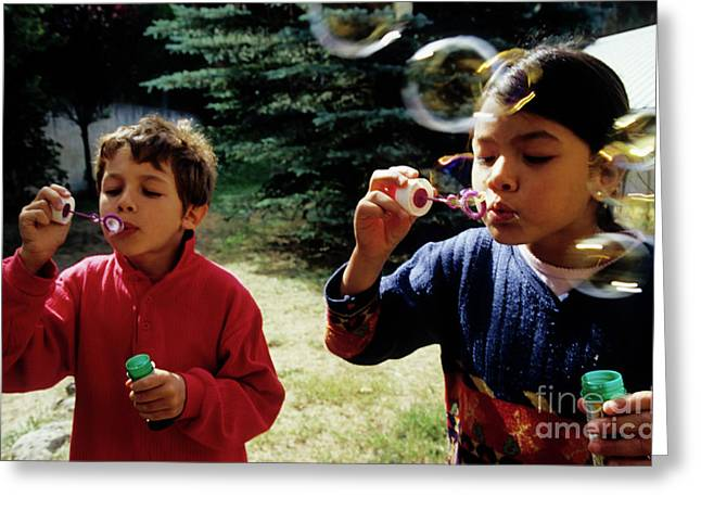 Multi-ethnic Greeting Cards - Girl and boy blowing bubble-wands Greeting Card by Sami Sarkis