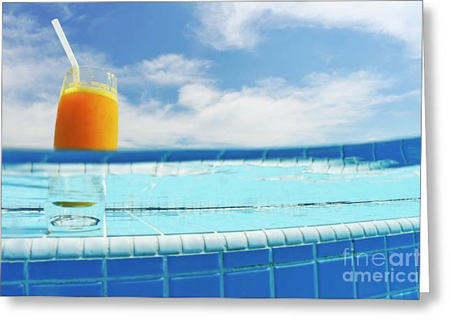Ledge Photographs Greeting Cards - Glass of orange juice on pool ledge Greeting Card by Sami Sarkis