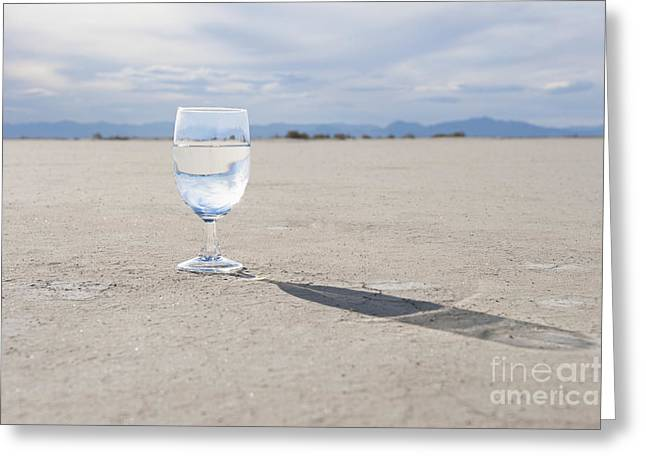 Casting A Shadow Greeting Cards - Glass of Water on Dried Mud Greeting Card by Thom Gourley/Flatbread Images, LLC