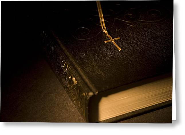 Gold Cross Pendant Resting On A Book Greeting Card by Philippe Widling