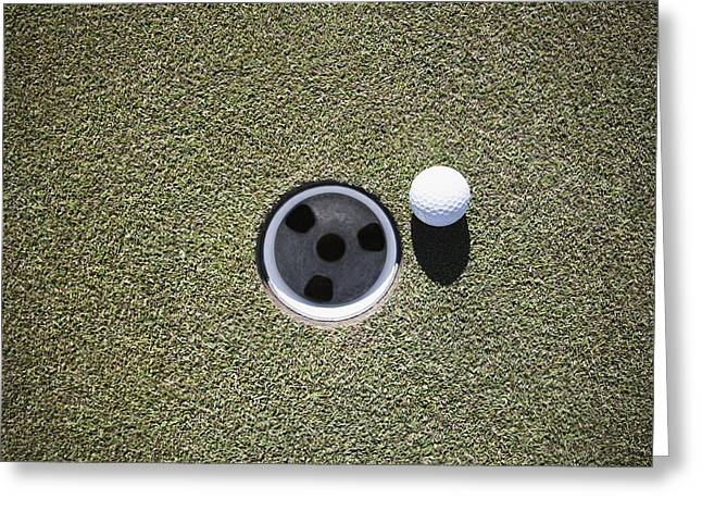 Casting A Shadow Greeting Cards - Golf Ball Next to a Putting Cup Greeting Card by Jetta Productions, Inc