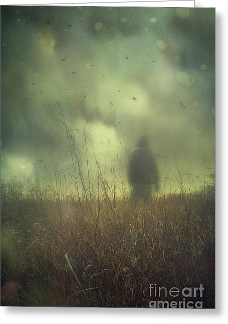 Depressed Greeting Cards - Hooded man walking in field with storm clouds Greeting Card by Sandra Cunningham