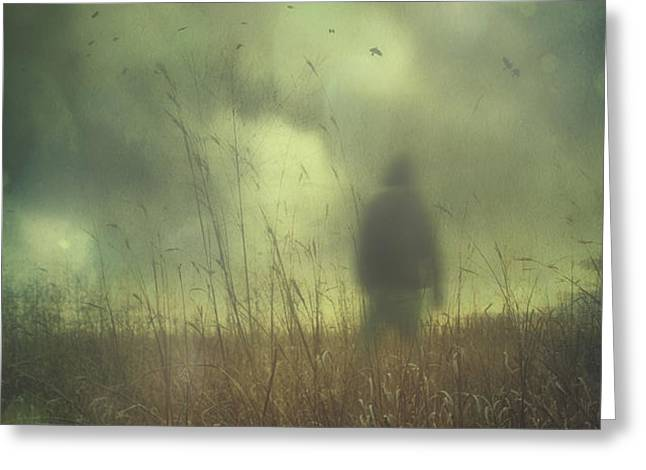 Hooded man walking in field with storm clouds Greeting Card by Sandra Cunningham