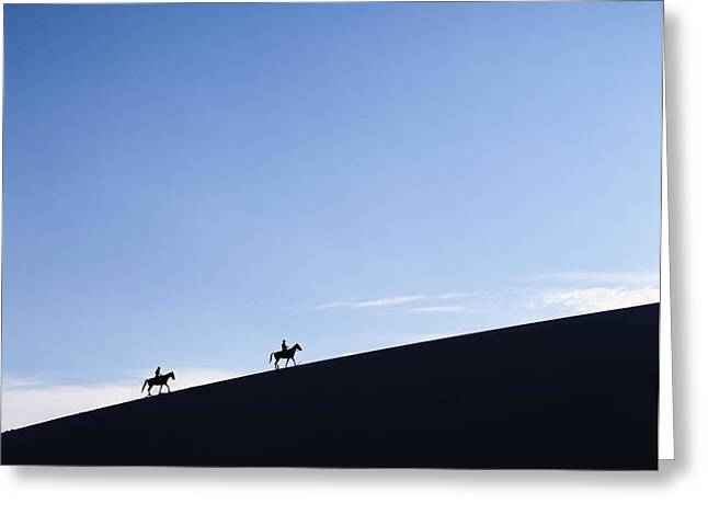 Silhouettes Of Horses Greeting Cards - Horse Riders At Dusk On A Sand Dune In Greeting Card by Axiom Photographic
