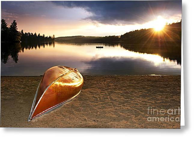 Canoe Greeting Cards - Lake sunset with canoe on beach Greeting Card by Elena Elisseeva