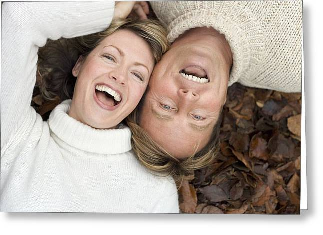Interpersonal Greeting Cards - Laughing Couple Lying On Autumn Leaves Greeting Card by Ian Boddy