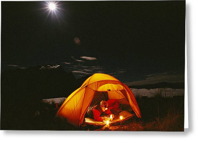 Moonlight Scene Greeting Cards - Man Reading In Tent At Night With Cerro Greeting Card by Gordon Wiltsie