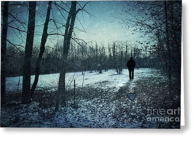 Man walking in snow at winter twilight Greeting Card by Sandra Cunningham