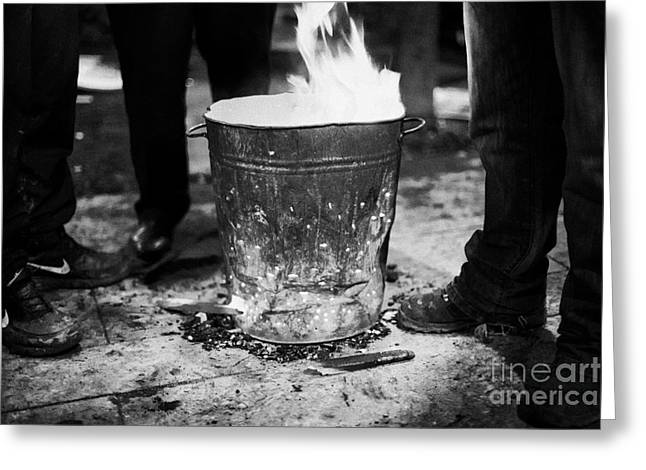 men standing around brazier burning wood and coal on a cold night in central belfast Greeting Card by Joe Fox