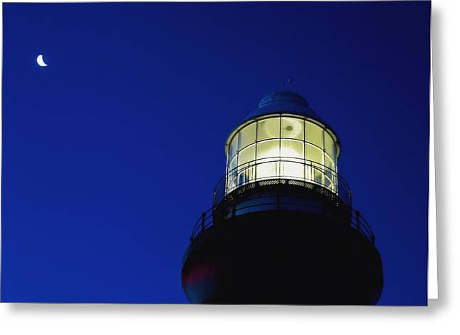 Illuminate Greeting Cards - Moon Crescent Above Lighthouse At Dusk Greeting Card by Axiom Photographic