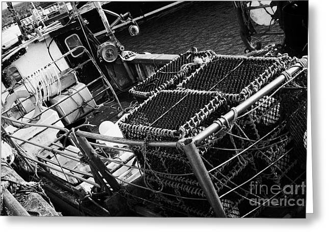 Lobster Pot Greeting Cards - new lobster pots piled up on the deck of a small fishing boat at John OGroats harbour scotland uk Greeting Card by Joe Fox