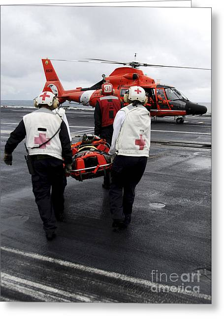 Rotary Wing Aircraft Photographs Greeting Cards - Personnel Carry An Injured Sailor Greeting Card by Stocktrek Images