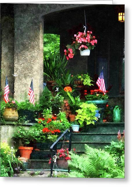 Geraniums Greeting Cards - Porch With Geraniums and American Flags Greeting Card by Susan Savad