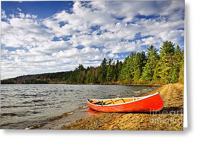 Canoeing Photographs Greeting Cards - Red canoe on lake shore Greeting Card by Elena Elisseeva