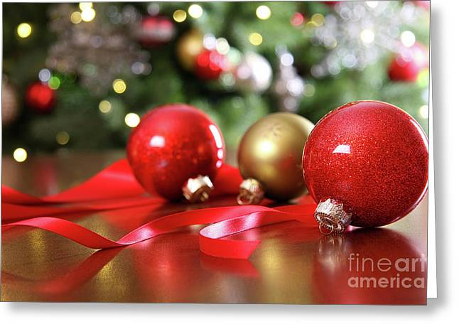 Backdrop Greeting Cards - Red Christmas ornaments on a table Greeting Card by Sandra Cunningham