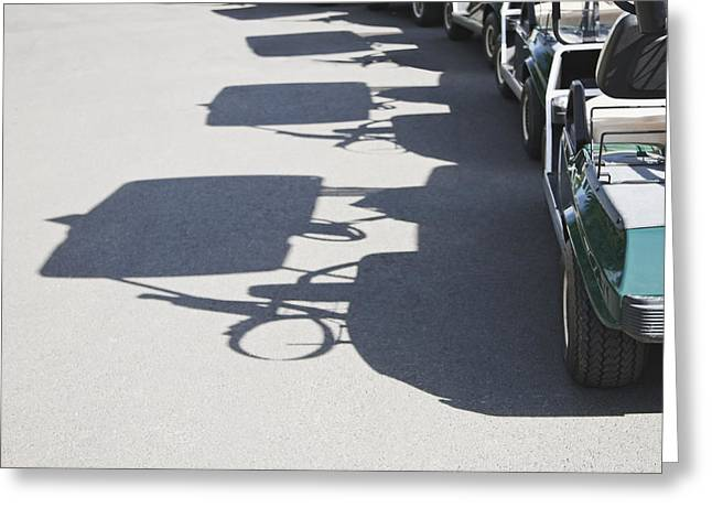 Casting A Shadow Greeting Cards - Row of Empty Golf Carts Greeting Card by Jetta Productions, Inc