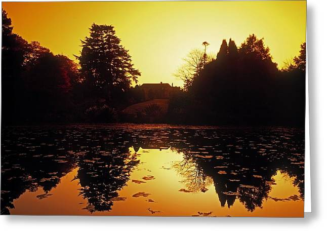 Sunset Reflecting In Water Greeting Cards - Silhouetted Home And Trees Near Water Greeting Card by The Irish Image Collection