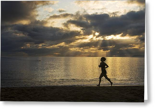 Jogging Greeting Cards - Silhouetted Woman Jogging On A Beach Greeting Card by Mattias Klum