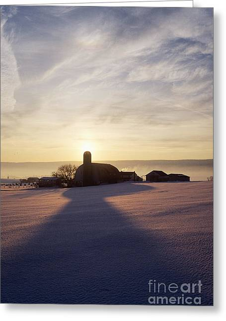 Snow Covered Field With Farm Silhouette At Sunset Greeting Card by Jeremy Woodhouse