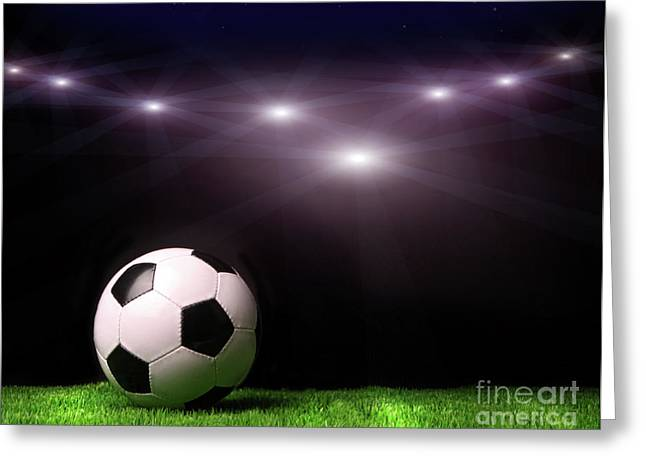 Spheres Greeting Cards - Soccer ball on grass against black Greeting Card by Sandra Cunningham