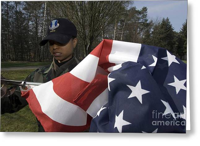 Best Sellers -  - Replacing Greeting Cards - Soldier Unfurls A New Flag For Posting Greeting Card by Stocktrek Images