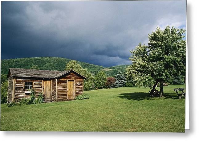 Lawns Fields Greeting Cards - Storm Clouds Form Above A Log Cabin Greeting Card by Raymond Gehman