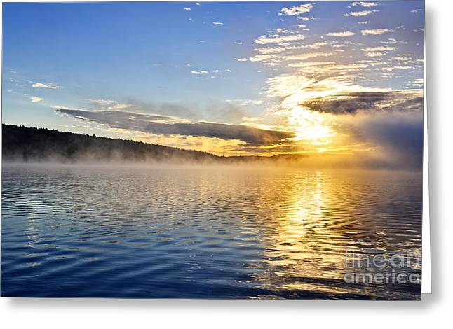 Sunrise. Water Greeting Cards - Sunrise on foggy lake Greeting Card by Elena Elisseeva