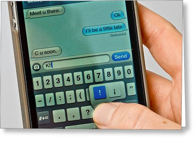 Texting On An Iphone Greeting Card by Photo Researchers