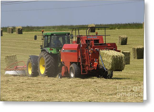Bailing Hay Greeting Cards - Tractor bailing hay at harvest time Greeting Card by Andy Smy
