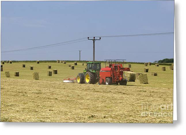 Bailing Hay Greeting Cards - Tractor bailing hay in a field at harvest time Greeting Card by Andy Smy