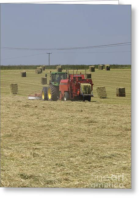 Bailing Hay Greeting Cards - Tractor bailing hay in a field at harvest time Pt Greeting Card by Andy Smy
