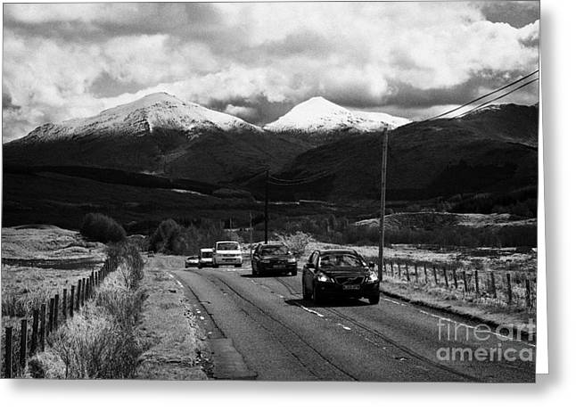 traffic on a82 trunk road through the scottish highlands with snow covered mountains ben more  Greeting Card by Joe Fox