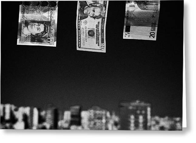 twenty pounds dollars euro banknotes hanging on a washing line with blue sky over city skyline Greeting Card by Joe Fox