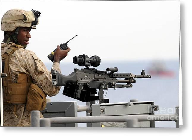 General Purpose Machine Guns Greeting Cards - U.s. Marine Talks On A Radio While Greeting Card by Stocktrek Images