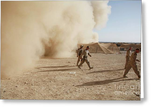 U.s. Marines Walk Away From A Dust Greeting Card by Stocktrek Images