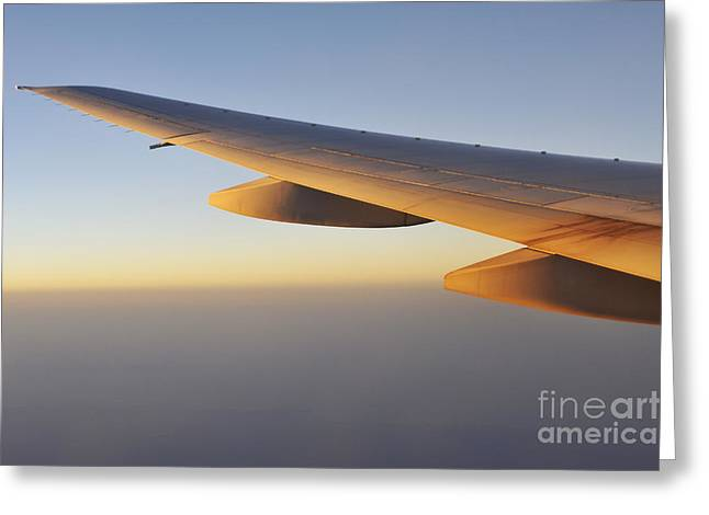 Aerospace Industry Greeting Cards - Wings of flying airplane over  clouds at sunset Greeting Card by Sami Sarkis