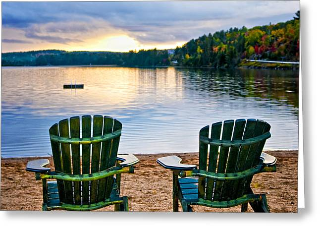 Beach Scenery Greeting Cards - Wooden chairs at sunset on beach Greeting Card by Elena Elisseeva