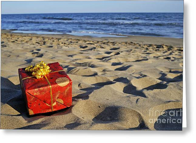 Surprise Greeting Cards - Wrapped gift box on beach Greeting Card by Sami Sarkis